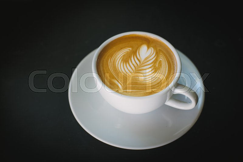 Coffee latte art make by barista in coffee shop cafe vintage color tone, stock photo