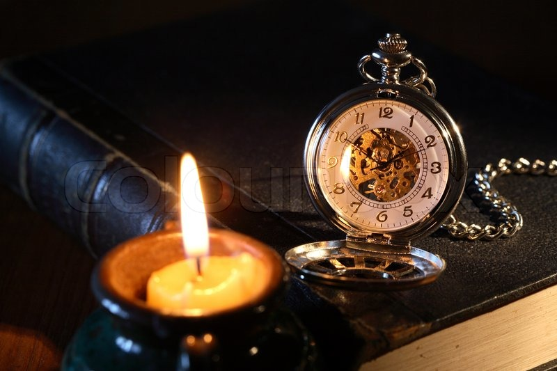 vintage pocket watch on book near lighting candle on dark