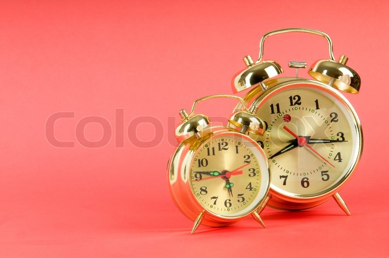 Time concept - alarm clock against colorful background, stock photo