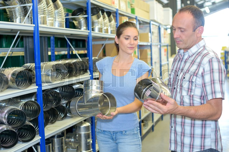 Man and woman in hardware store looking at metal flues, stock photo