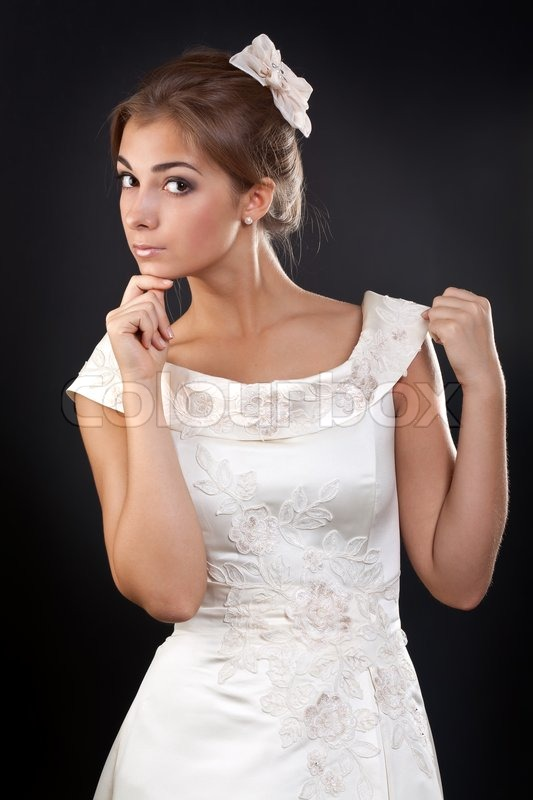 Girl In A White Wedding Dress In The Studio On A Black Background