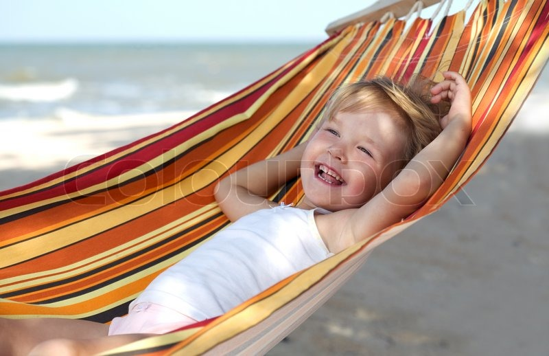 child relaxing in a hammock on the sea beach   stock photo   colourbox  rh   colourbox