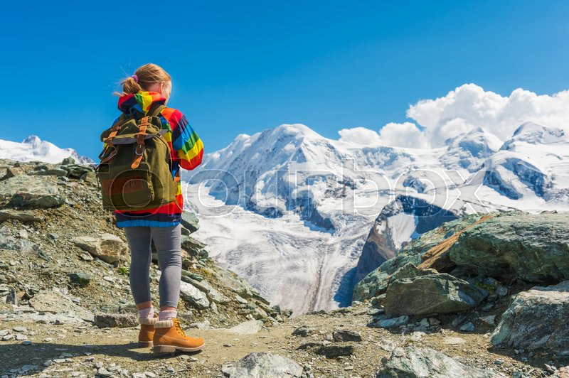 Cute little girl wearing backpack and colorful coat, standing in front of Gornergrat glacier, Switzerland, back view, stock photo