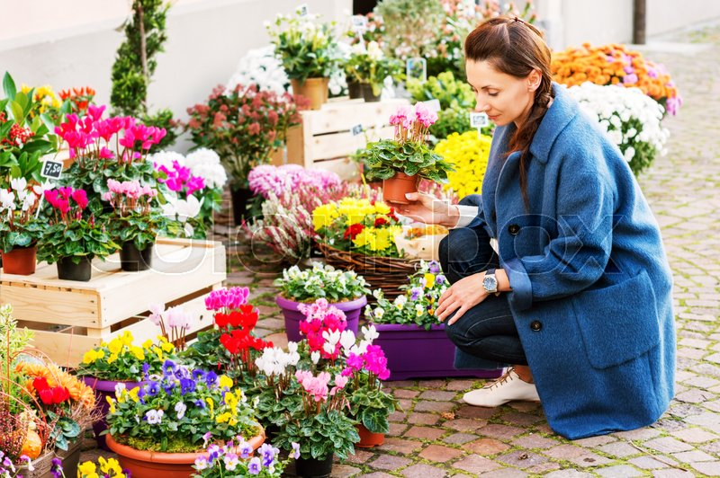 Woman buying flowers in pots in flower shop, stock photo
