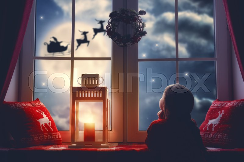 Merry Christmas and happy holidays! Cute little child girl sitting by window and looking at Santa Claus flying in his sleigh against moon sky. Room decorated on Christmas. Kid enjoy the holiday. , stock photo