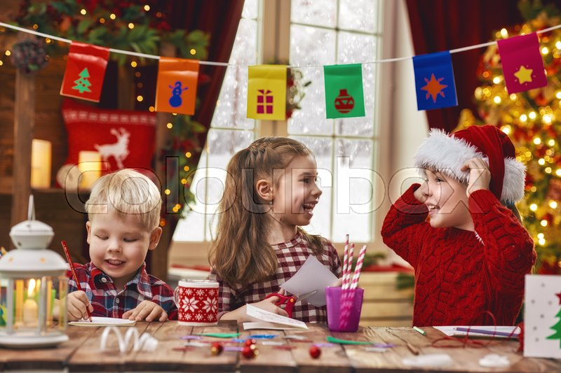 Merry Christmas and Happy Holidays. Adorable little children make cards, gifts and decorations for the holiday. Cute kids are engaged in creativity, stock photo