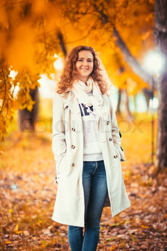 Young girl in a light coat on the background of autumn park, stock photo
