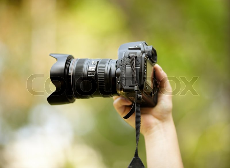 Hand of man with black professional camera, natural light, selective focus on nearest part, stock photo
