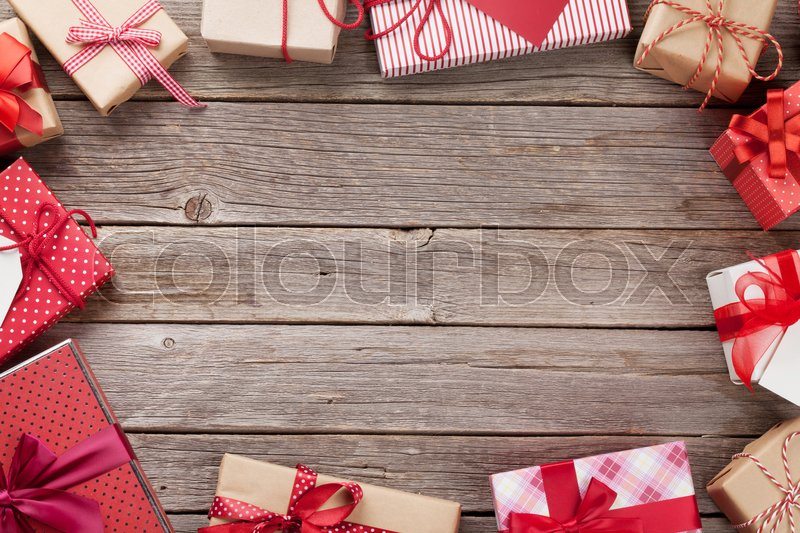 Christmas gift boxes frame greeting card on wooden table. Top view with copy space for your greetings, stock photo