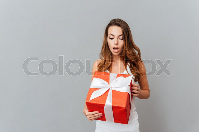 Cute surprised young woman open present box isolated on a gray background, stock photo