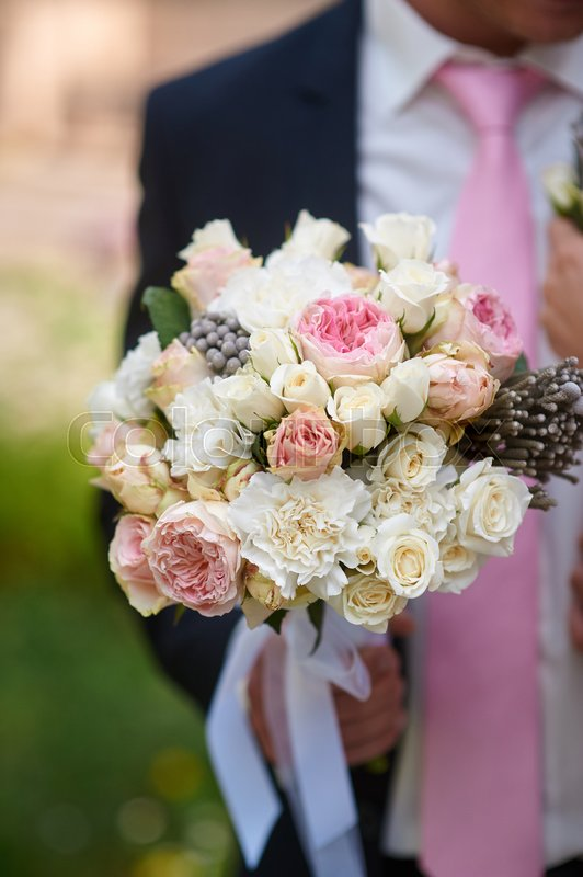 Groom holds the beautiful bride bouquet in wedding morning, stock photo