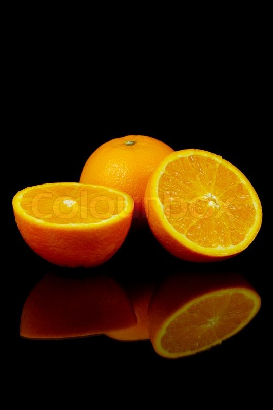 fresh oranges isolated against a black background stock