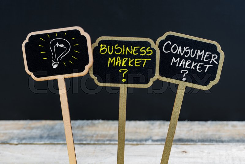 Concept message BUSINESS MARKET versus CONSUMER MARKET and light bulb as symbol for idea written with chalk on wooden mini blackboard labels, defocused chalkboard and wood table in background, stock photo