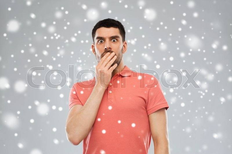 Emotion, fear, winter, christmas and people concept - scared man in polo t-shirt over snow on gray background, stock photo