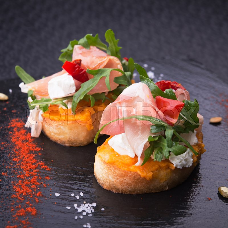 Stock image of 'delicious bruschetta with prosciutto, tomatoes and arugula on a stone slate. restaurant food'