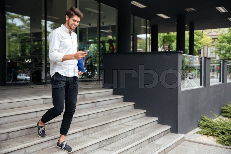 Smiling attractive young businessman walking and using mobile phone near business center, stock photo