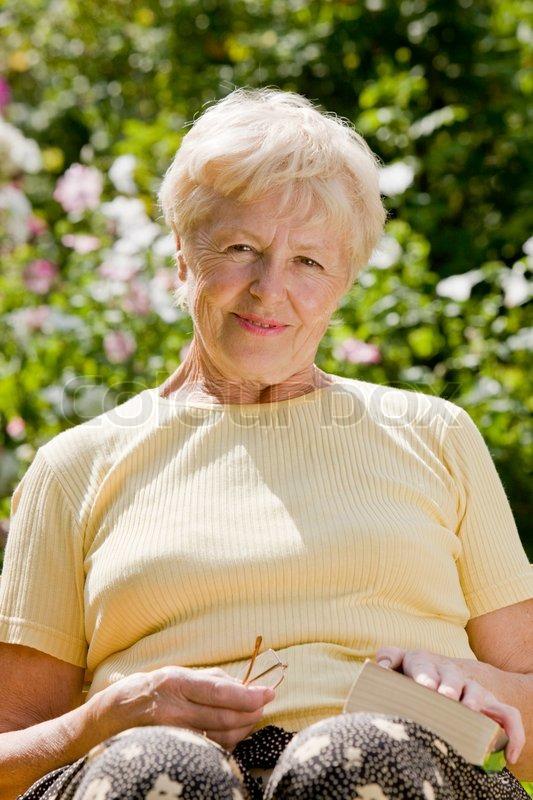 Die ältere Frau liest das Buch in einem    Stock Bild