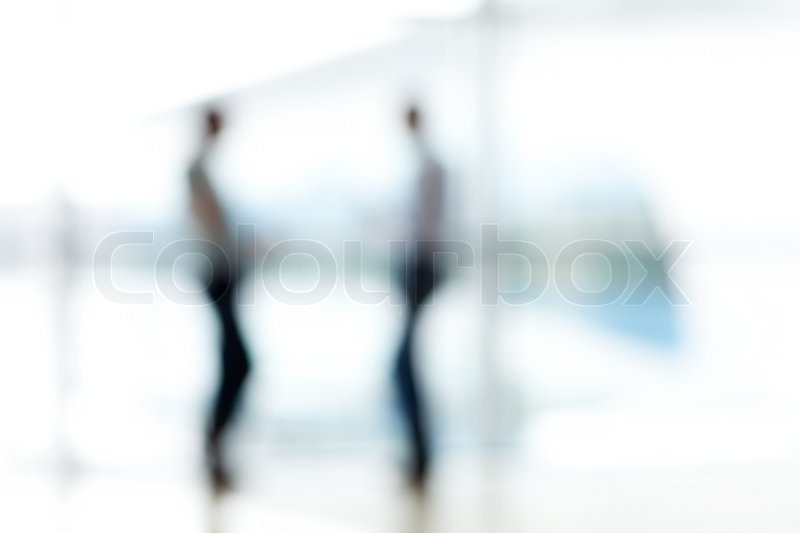 Stock image of 'Two mans silhouette in hall of office building'