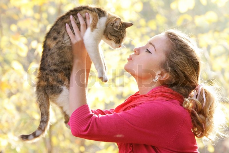Young attractive girl with cat on natural background, stock photo