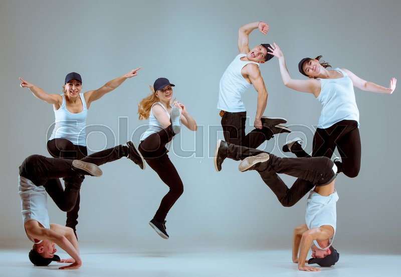 Group of men and women dancing fitness or hip hop choreography in gray studio background, stock photo