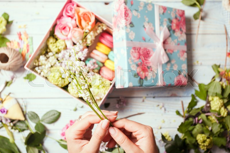 Preparation of flower box with macaroons, top view of florist workplace, stock photo