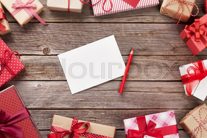 Christmas gift boxes and greeting card on wooden table. Top view with copy space. Gift wrapping, stock photo