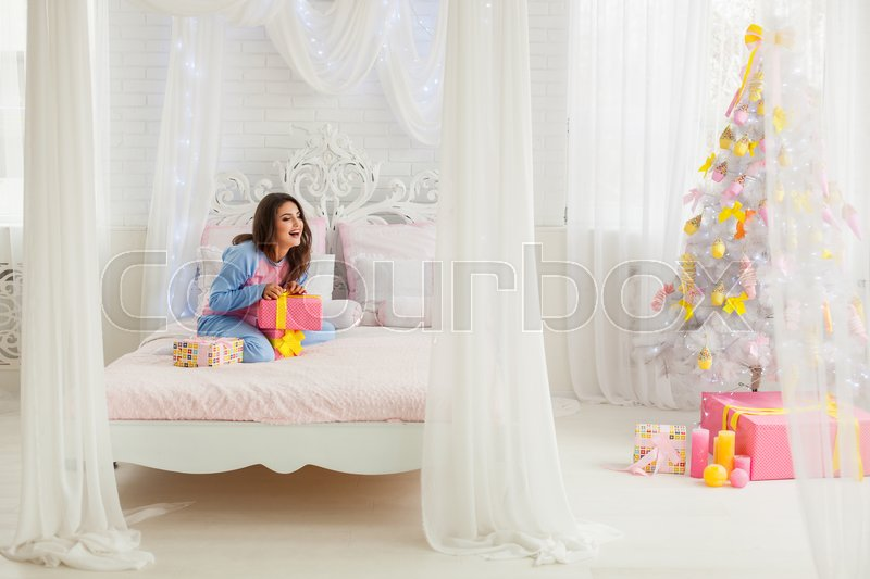 Laughing model opening presents in bed near christmas tree, stock photo