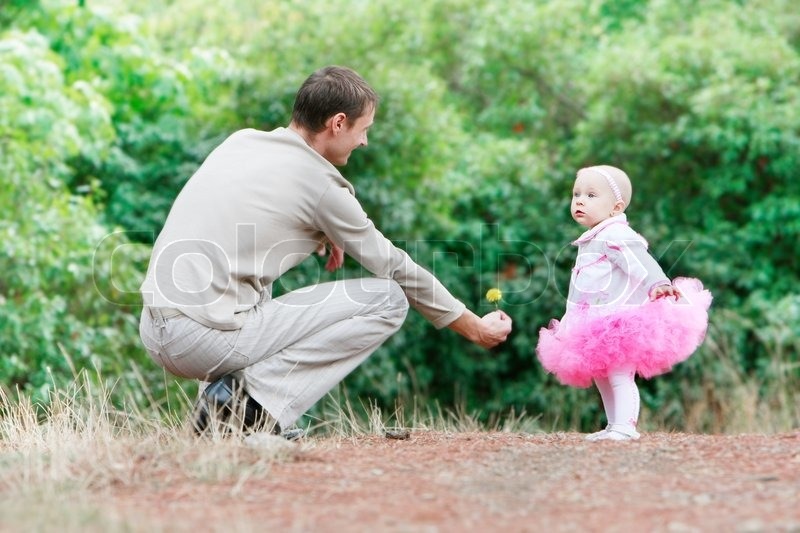 father giving a flower to his daughter stock photo colourbox