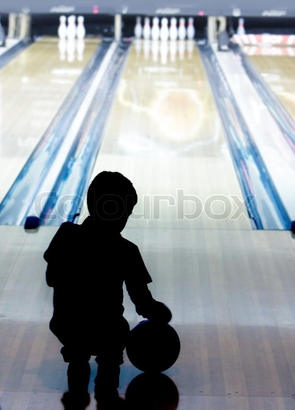Stock image of 'Silhouette of young boy playing bowling'