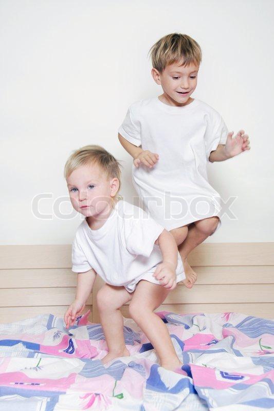 zwei kinder springen auf bett der eltern stockfoto colourbox. Black Bedroom Furniture Sets. Home Design Ideas