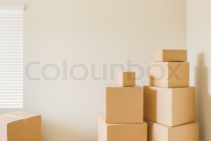 Variety of Packed Moving Boxes In Empty Room with Room For Text, stock photo