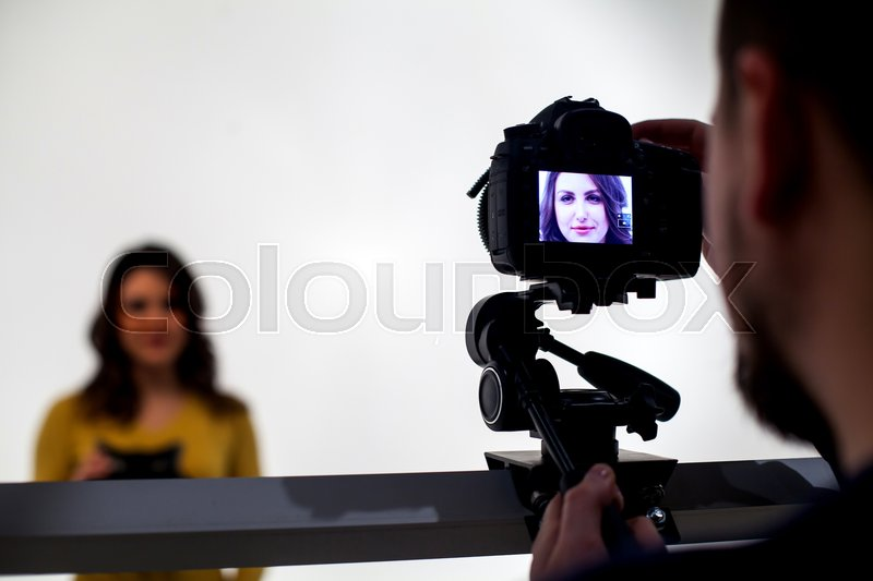 Backstage from video studio with woman going to wear virtual reality headset on white background, stock photo