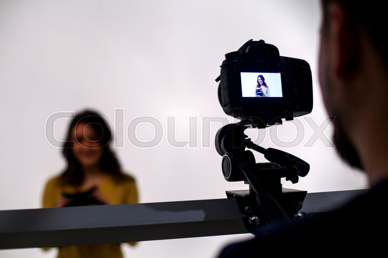 Backstage from video studio with woman going to wear virtual reality headset, stock photo