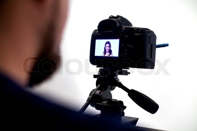 Backstage from video studio. Photografer works with camera, stock photo