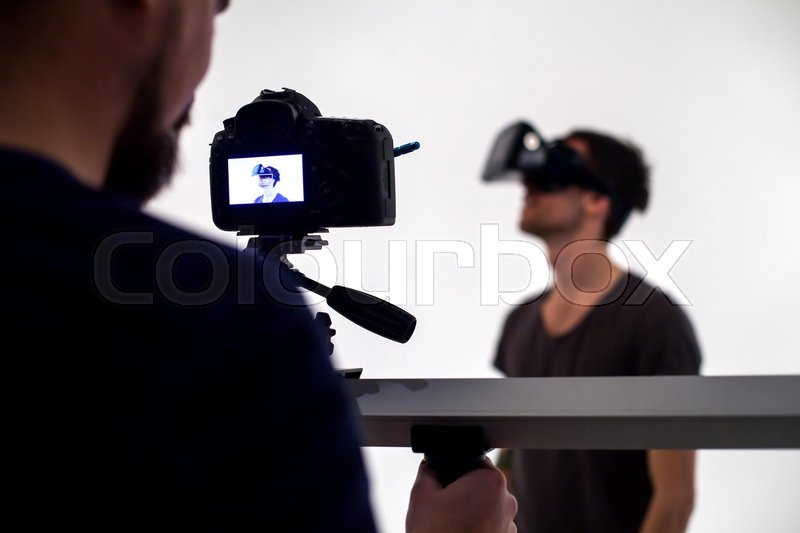 Backstage from video studio with man looking through virtual reality headset, stock photo