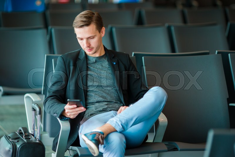 Urban business man talking on smart phone traveling inside in airport. Casual young businessman wearing suit jacket. Handsome male model. Young man with cellphone at the airport while waiting for boarding, stock photo