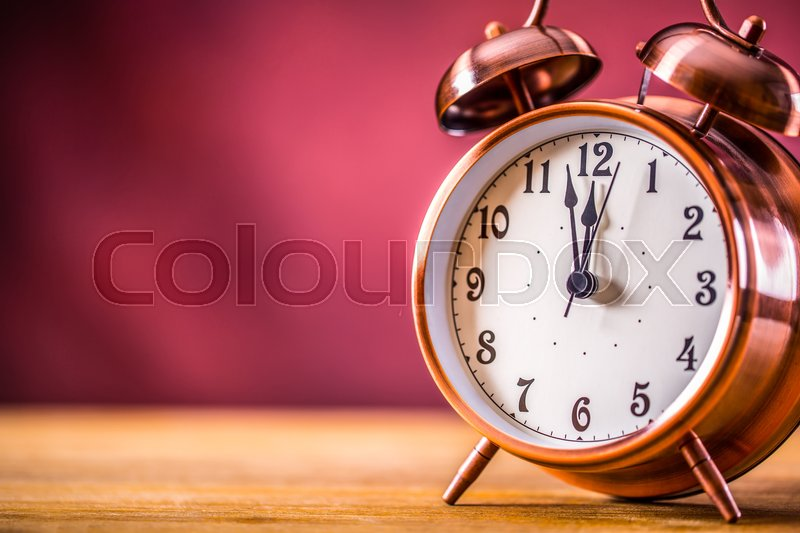 Retro alarm clock with two minutes to midnight. Filtered photo in vibrant colors 50s to 60s. Pink background, stock photo