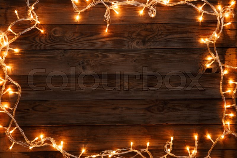 Christmas postcard with garland on empty brown background, stock photo