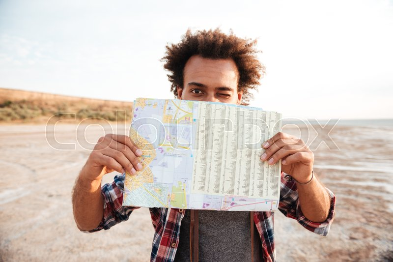 Joyful african american young man covered his face with map and winking, stock photo