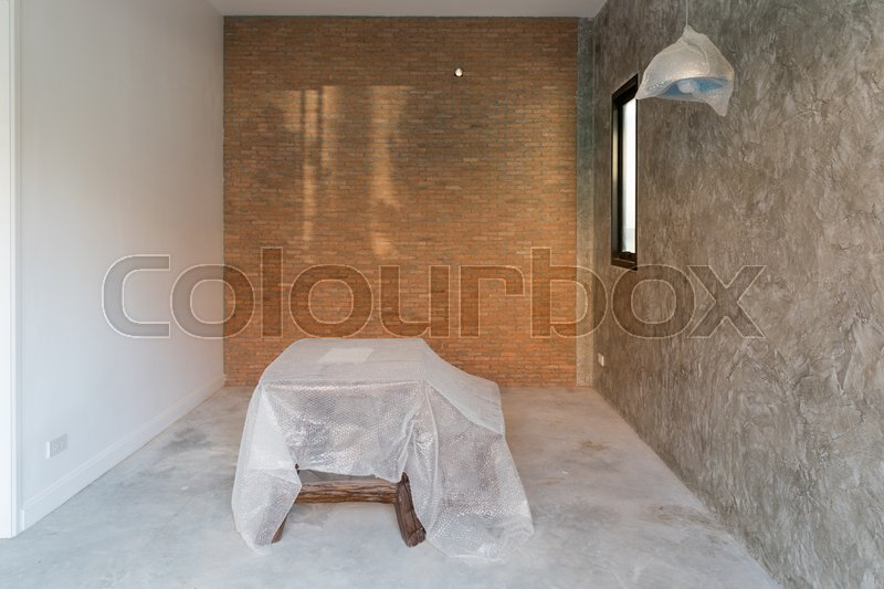 Room interior in renovation with cement floor and red brick wall background, stock photo