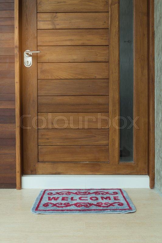 Very best Welcome door mat infront of teak wooden door background | Stock  DU16