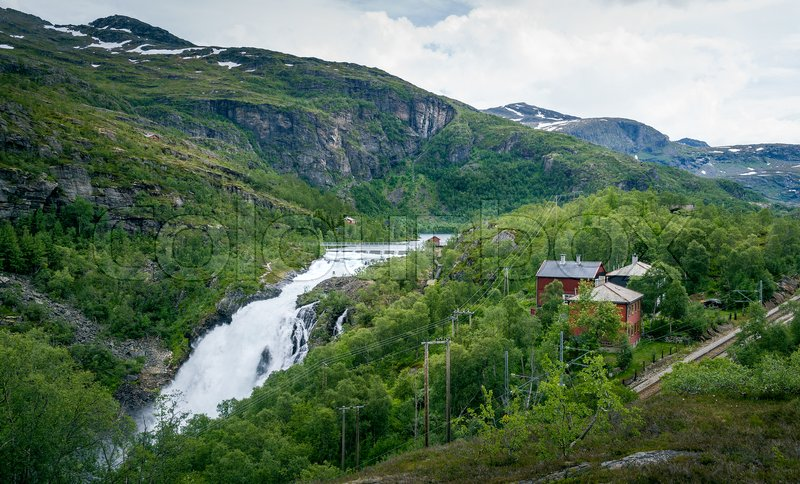 Kjosfossen waterfall valley landscape. Waterfall dam, village houses and famous Flamsbana railway. Flam, Aurland, Norway, stock photo