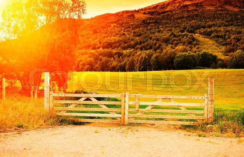 Autumn farm entrance gate with light leak background hd, stock photo