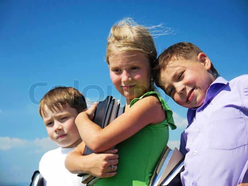 Three friends holding textbooks over blue sky background, stock photo