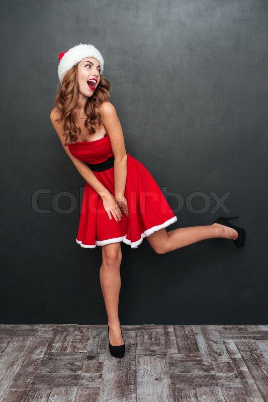 Girl with Santa hats standing on one leg. Santa\'s helper. Santa\'s dress, stock photo