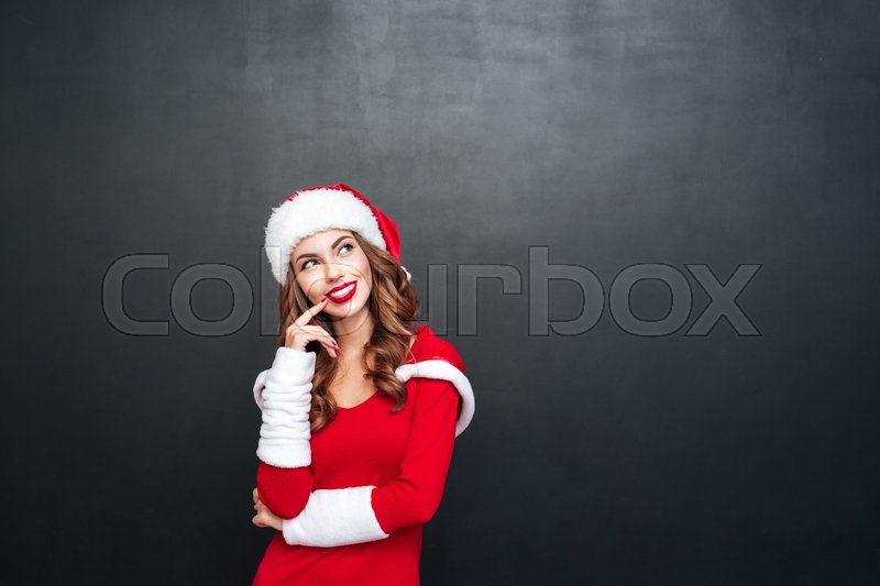 Portrait of beautiful wondered woman in red dress and hat looking away isolated on a black background, stock photo