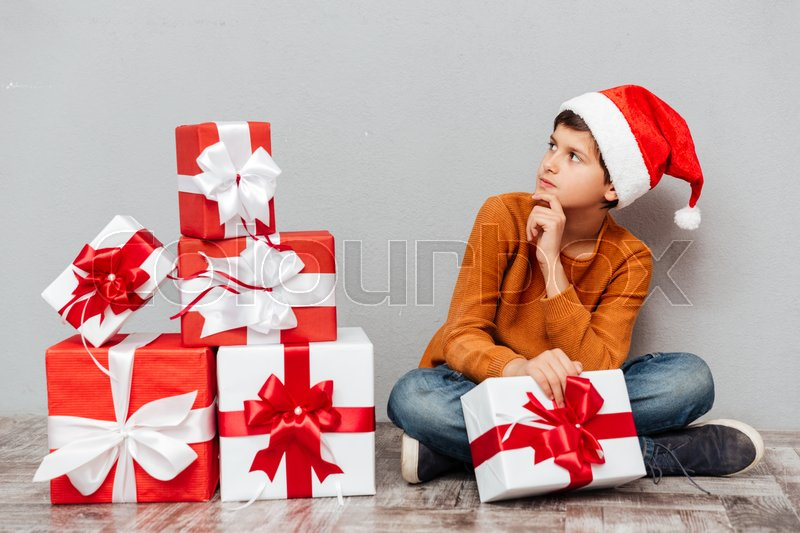 Thoughtful boy in santa claus hat with gift box sitting and looking away, stock photo