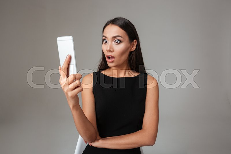 Shocked young woman in black dress looking at mobile phone over gray background, stock photo