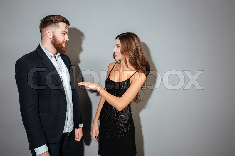 Young attracctive couple in smart wear talking to each other over gray background, stock photo