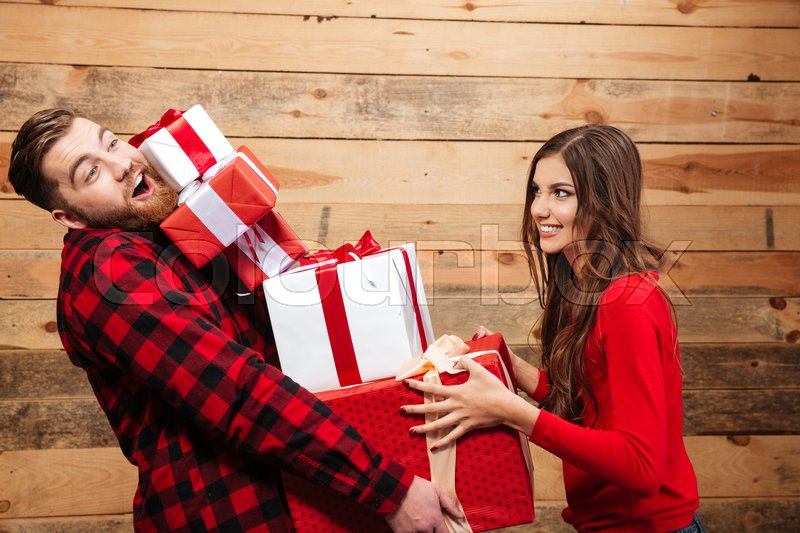 Happy funny couple standing with heap of xmas present boxes isolated on a wooden background, stock photo